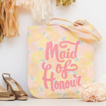 A pastel floral canvas tote bag with the words maid of honour printed in pink on the front in a hand drawn style leant against a wall at a wedding surrounded by wedding decorations
