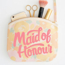 A floral canvas pouch with the words maid of honour printed in pink in a hand drawn style with makeup and everyday objects poking out of the top