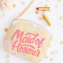 A floral canvas pouch with the words maid of honour printed in pink in a hand drawn style layed on a table at a wedding with lipstick next to it and surrounded by confetti