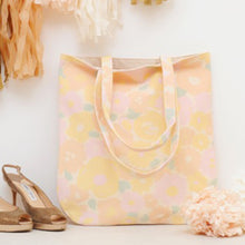 A pastel coloured floral canvas tote bag leant against a wall surrounded by wedding decorations