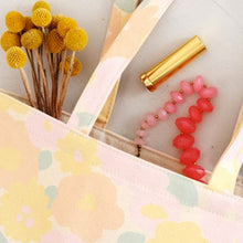 A close up image of a pastel coloured floral canvas tote bag with flowers and makeup spilling out