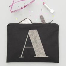 "A black canvas pouch with the initial ""A"" printed on it in multi-coloured glitter with makeup and other daily essentials items spilling out of it"
