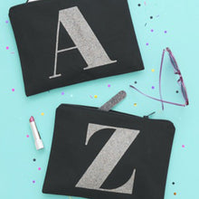 "Two black canvas pouches with the initial ""A"" and ""Z"" printed on them respectively in multi-coloured glitter with makeup and other daily essentials items spilling out of them"