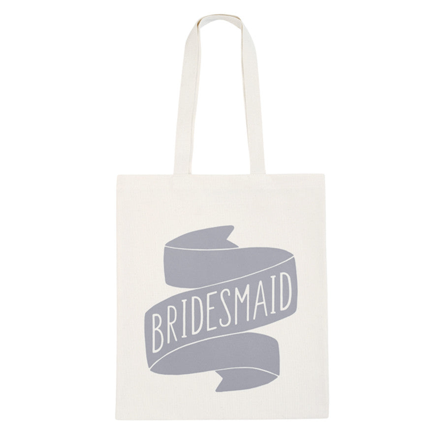 A canvas tote bag with the word Bridesmaid inside a ribbon printed on it in grey