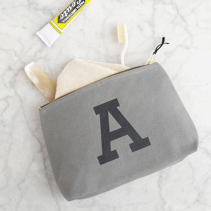Heavy grey canvas wash bag with the initial 'A' printed in black