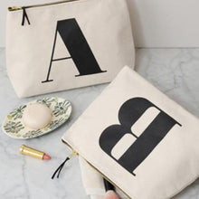 Natural canvas wash bags with the Initial 'A' printed in black in a traditional font on one and the letter 'B' on the other on a marble surface in a bathroom setting