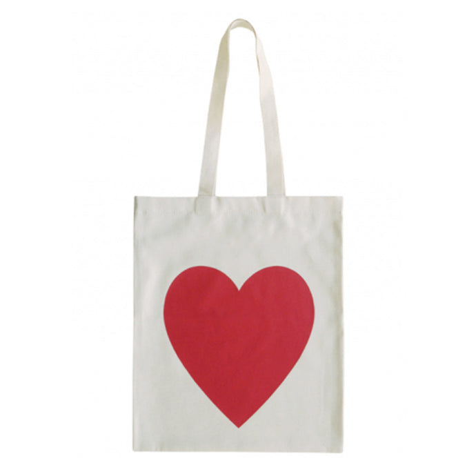 A natural cotton canvas tote bag with a bold heart screen printed in red ink on one side
