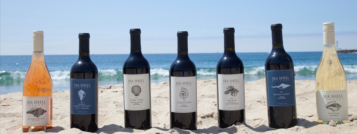 7 bottles of Sea Shell Cellars Wine sitting in the Sand on the beach in Paso Robles, CA