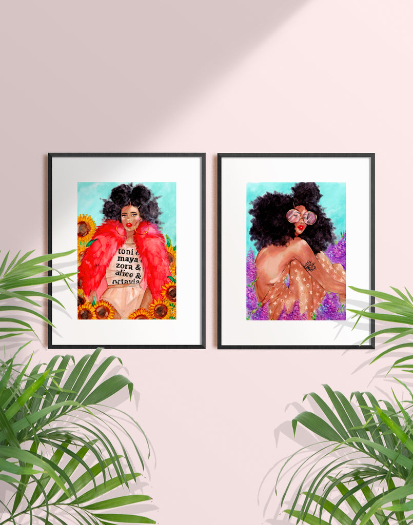 Two framed illustrations of beautiful black women with big curly natural hair sitting among flowers by Tatiana Poblah