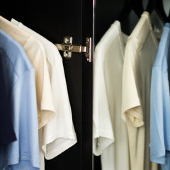 Picture of coloured undershirts hanging in wardrobe