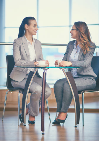 Two women in business suits talking over coffee
