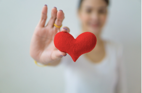 A woman holding a red heart
