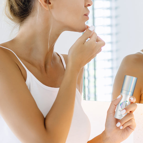 Woman applying her Ópalens Face Serum