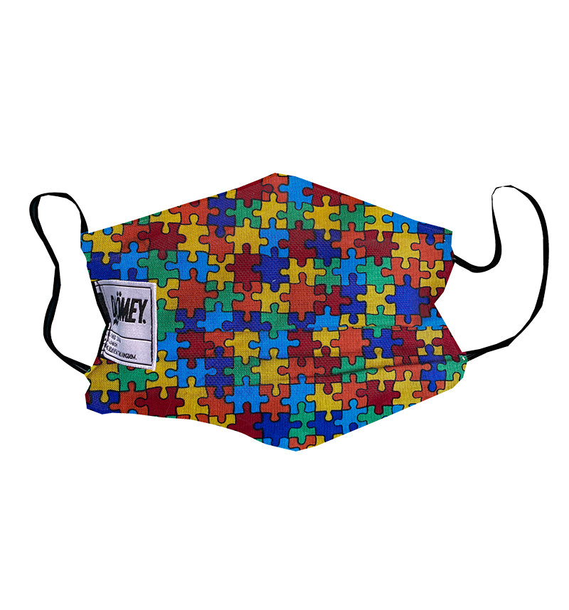 Face mask with multi-colour puzzle pieces on it
