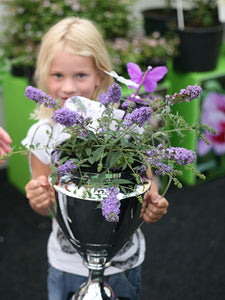 A young girl holds a silver trophy cup with a Lo and Behold Lilac Chip butterfly bush in it
