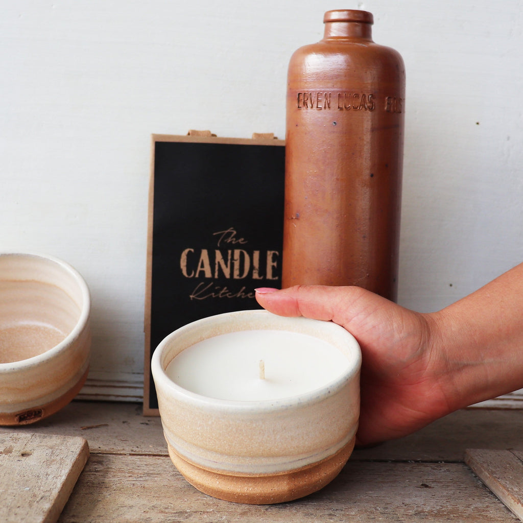 The Candle Kitchen hand holding a  ceramic bowl filled with a soy way candle  shown with an empty reusable bowl
