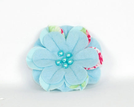 Soft felt flower brooch in sky blue with printed cotton inset petals in blue and pink rose design. Sky blue pearl beads at the centre.