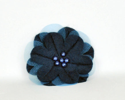 Navy soft felt flower brooch with sheer inset petals and pearl beads at the centre.