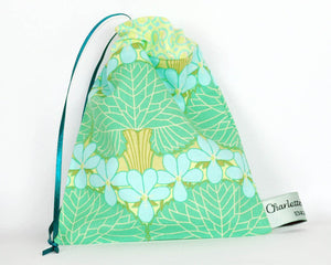 100% cotton print pouch made with green and blue printed cotton with a ribbon pull cord for storing nursing pads and soothers.