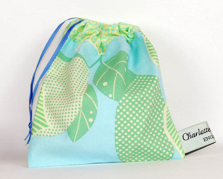 100% cotton print pouch made with green and blue printed cotton with a purple ribbon pull cord for storing nursing pads and soothers.