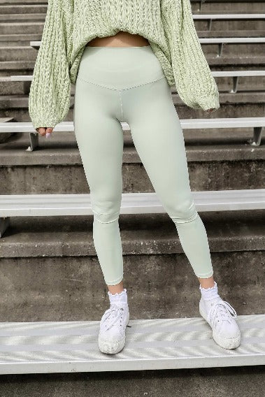 Sea Foam Green Leggings, model standing on bleachers