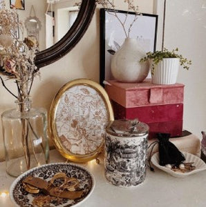 candle, picture frame, mirror, trinket trays, flowers sitting on dresser top