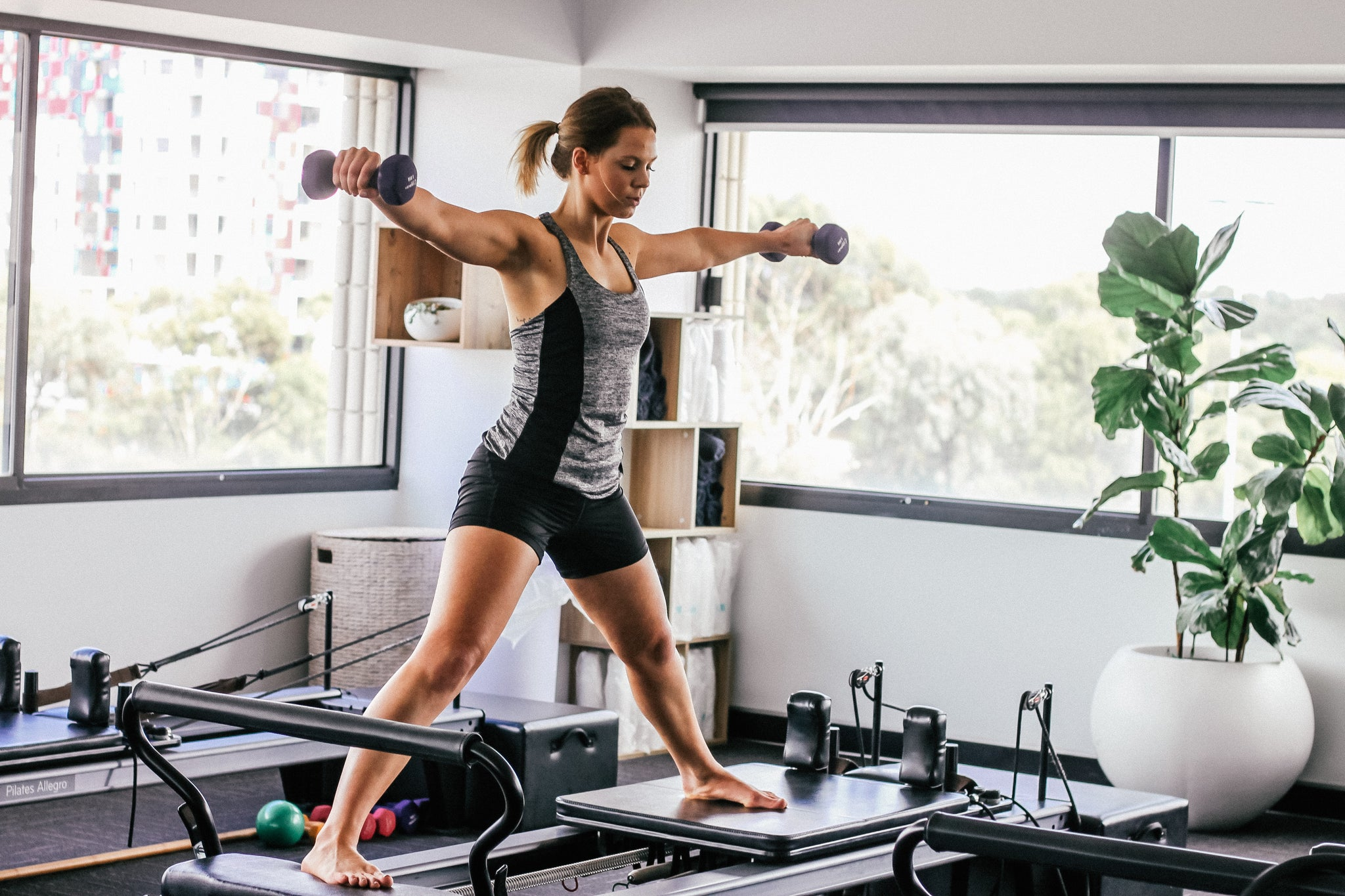 Woman standing on a Pilates reformer