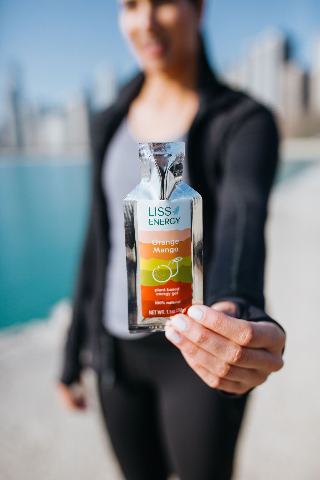 Woman holding orange mango energy gel