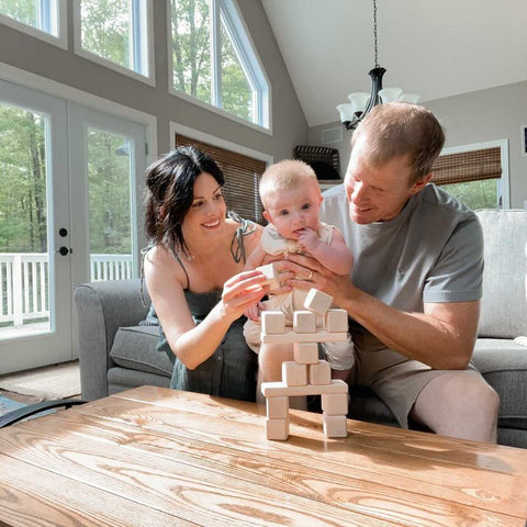 A mom, dad, and baby play with handmade wooden blocks in a sunlit living room.