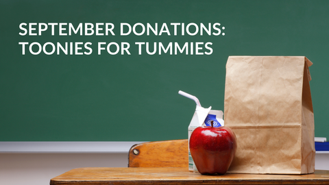 """An apple, carton of milk, and brown bag sit on a desk in front of a green chalk board. Text reads """"September Donations: Toonies for Tummies"""""""