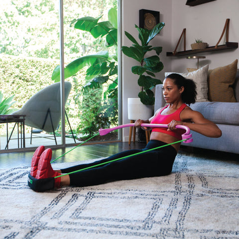 a woman performs resistance band training at home