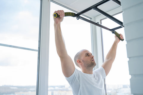 man using a pull up bar in his home gym