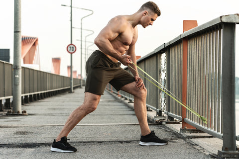 man doing portable resistance band strength training outdoors
