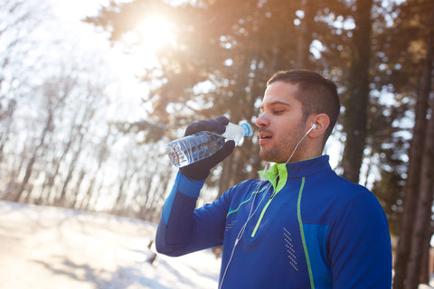 man drinking water during winter exercise