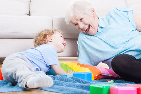 cheerful grandmother playing with a small child on the floor