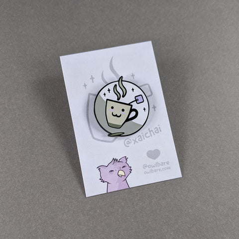 The xaichai enamel pin depicts a cute coffee mug with chai teabag hanging out. The mug is hella kawaii and smiling with rosey cheeks. The pin has one post and comes with a black rubber clutch and purple backing card.
