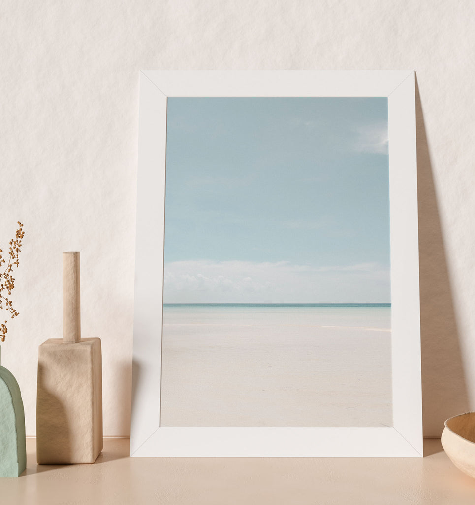 light blue beach and white sand with dark blue ocean photo art print in white frame leaning on shelf