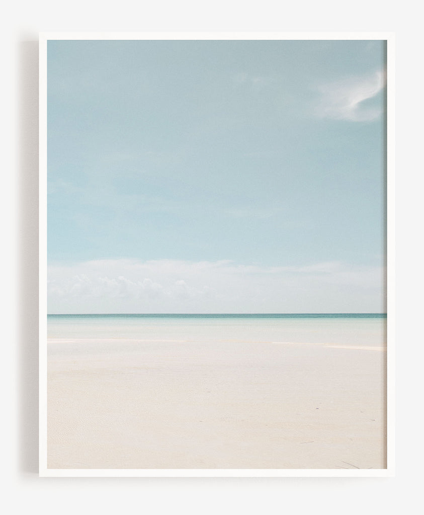 light blue beach and white sand with dark blue ocean photo art print in white frame