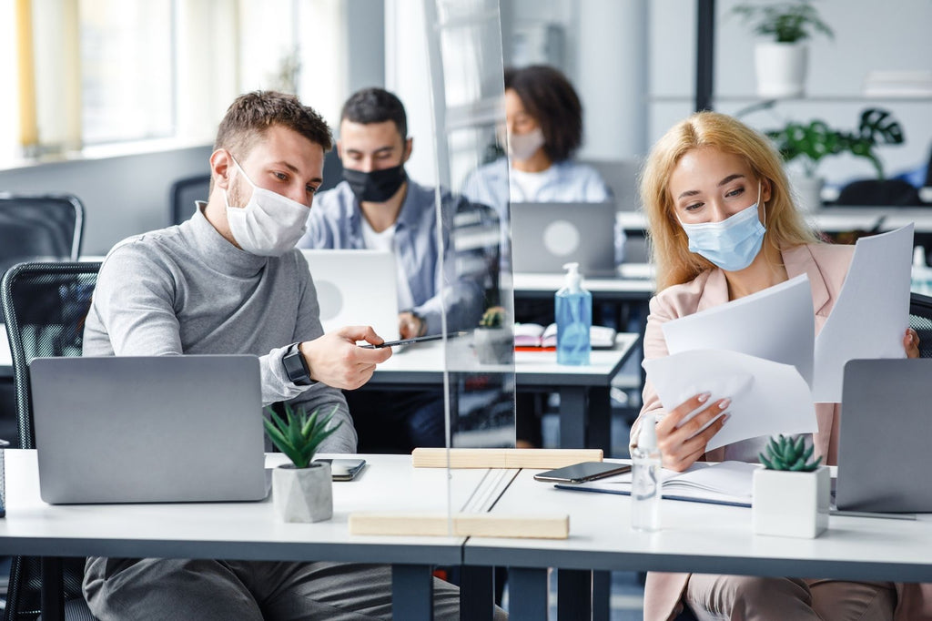 colleagues in the office, sneeze guard separates work space