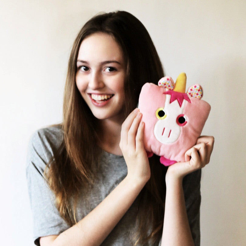 Plush toy unicorn stuffed animal with a useful back pocket, designed by young entrepreneurs