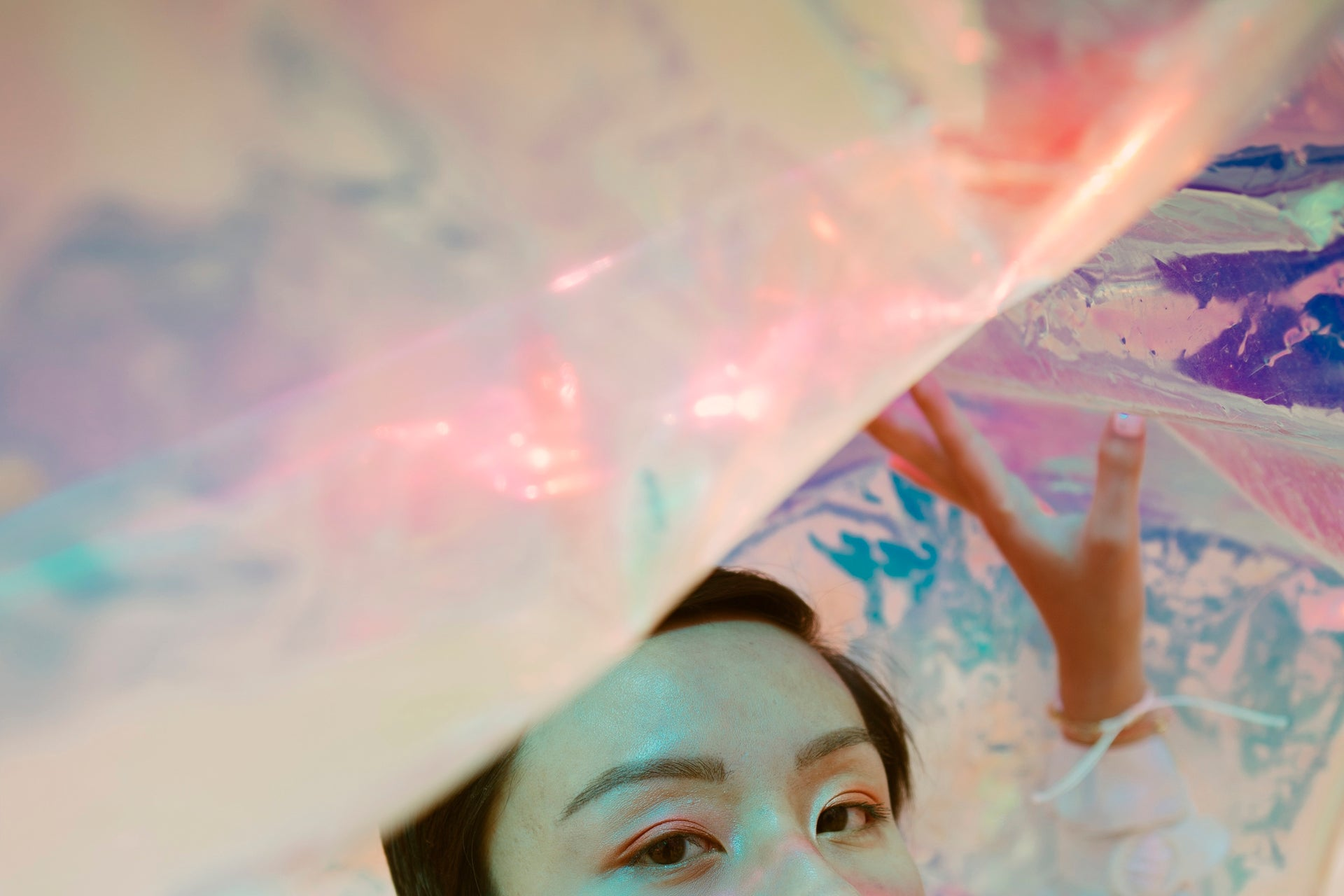 Young person stands beneath a holographic material | Kinship