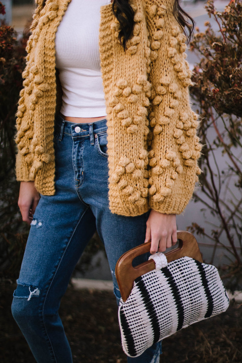 Pom Pom sweater, distressed jeans, crocheted handbag with wooden handle. Bohemian, classy style with name brand clothing in an independent and local boutique.
