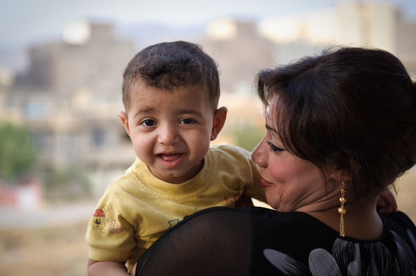 Iraqi woman holding her son, an artisan making handcrafted pillar candles for Propserity Candle in Baghdad