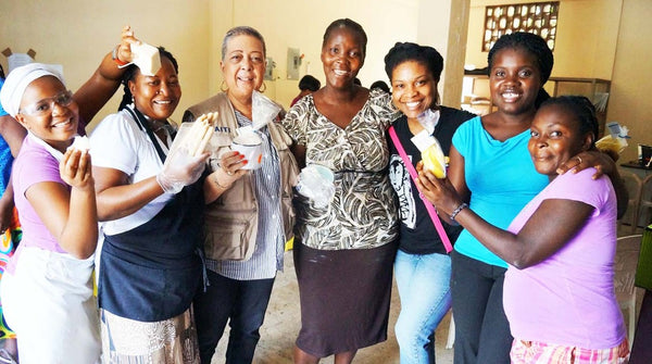 Haitian women artisans holding handpoured fair trade candles for Prosperity Candle