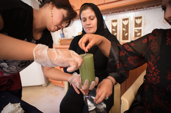 Iraqi women artisans making soy blend fair trade pillar candles for Prosperity Candle in Baghad
