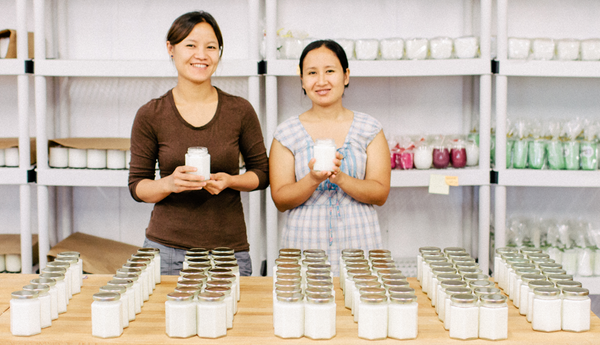 Moo Kho and Naw holding their handmade fair trade soy blend artisan candles at Propserity Candle