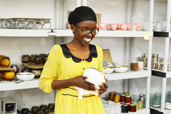 Meet women artisan Lydia of Prosperity Candle, who is cleaning and gift wrapping fair trade soy candles that give back