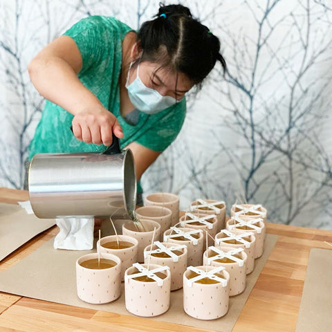 Candle-maker Sai Aye, originally from Burma, pouring soy coconut candles at Prosperity Candle