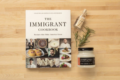 Socially responsible gift highlighting Immigrant Cookbook set that includes a fairtrade soy blend kitchen candles hand poured by artisans creating a brighter future in the United States. Best culinary gift.