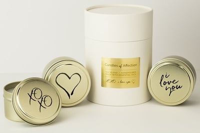 Soy blend travel candles featuring words of affection throughout the year. Beautiful packaging. Each fair trade candle is hand poured by a woman refugee in the United States. Best Valentine's Day present with a mission.